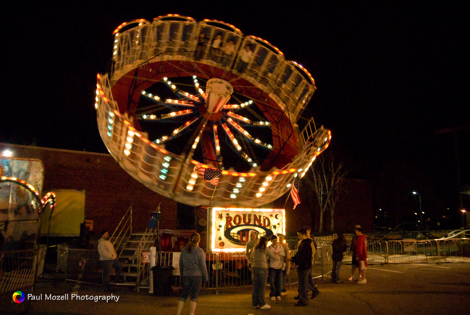 Teenagerrs at a small-town carnival at night.